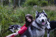 Woman in red dress with tree wolfs in forest Stock Photo