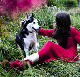 Woman in red dress with tree wolfs, forest, husky dogs mystery p Stock Photo