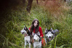 Woman in red dress with tree wolfs in forest Stock Image
