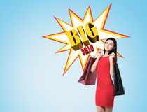 Woman in red dress with two shopping bags near big sale poster o Royalty Free Stock Photo