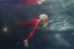 Woman in red dress under water. Blonde woman in a red dress under the water Royalty Free Stock Image
