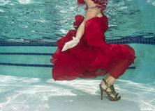 Woman in a red dress underwater Stock Images