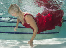 Woman in a red dress underwater Stock Photography