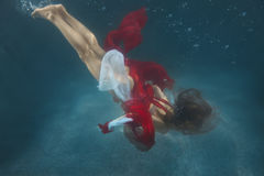 Woman in red dress underwater. Royalty Free Stock Photos
