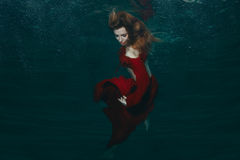Woman in red dress underwater. Royalty Free Stock Photography