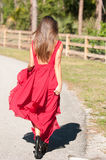 Woman in a red dress walking away Royalty Free Stock Photos