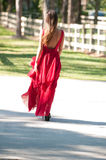 Woman in a red dress walking away Stock Images