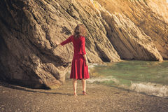 Woman in red dress walking on the beach Stock Photos