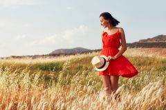 Woman in a red dress walking on the field on a warm summer evening. Yellow grass at sunset, the girl holding a hat in his hands Royalty Free Stock Photography