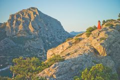 Woman in red dress walking on rock. Outdoor lifestyle photo of woman in red dress walking on rock. Travel background. Tourism Royalty Free Stock Photography