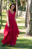 Woman in a red dress walking towards camera Stock Photo