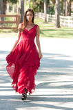 Woman in a red dress walking towards camera Stock Images