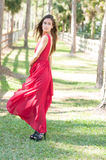 Woman in a red dress walking towards camera Royalty Free Stock Photos