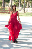 Woman in a red dress walking towards camera Royalty Free Stock Images