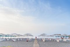Woman in red dress walking on wooden path to the sea among a lot of deck chairs and umbrellas on the sides. royalty free stock images