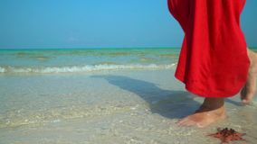 The woman in a red dress walks on the coast with white sand. Woman in red dress on the tropical beach. Starfish on phu. On this video you can uvdet as the woman stock video footage