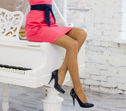 Woman in a red dress on a white piano Stock Images