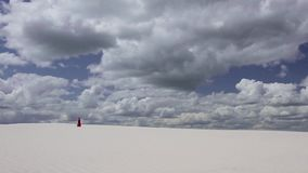 Woman in red dress on white sand against the blue sky. Woman in the red dress is by white sand against the blue sky with white clouds stock footage