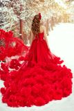 Woman Red Dress and Winter Snow, Fashion Model in Ruched Fluffy Waving Gown, Rear View. Woman Red Dress and Winter Snow, Fashion Model in Ruched Fluffy Waving royalty free stock image