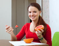 Woman in red eats grapefruit at home stock image