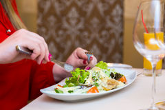 Woman in red eats salad natural. Healthy eating and diet royalty free stock photo