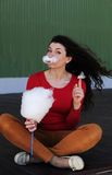 Woman in red. The woman in the red eats sweets with black long hair Stock Image