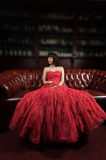 Woman in red evening dress sitting on the sofa Royalty Free Stock Photo