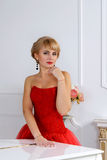Woman in a red evening dress standing near piano Royalty Free Stock Image