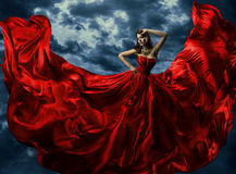 Woman in red evening dress, waving gown with flying long fabric. Over artistic sky background Stock Photos
