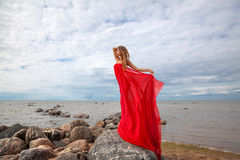 Woman with red fabric on sea beach Royalty Free Stock Photography