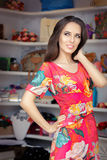 Woman in Red Floral Dress in Fashion Store. Portrait of a trendy girl in a fashion boutique Royalty Free Stock Photography