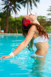 Woman with red flower in the pool Stock Photography