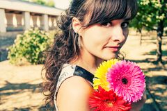 Woman with red flower walking with flowers in her hands Royalty Free Stock Image