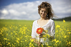 Woman with red flowers in rapeseed field. Royalty Free Stock Images