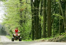 Woman in red on four wheeler Royalty Free Stock Photo