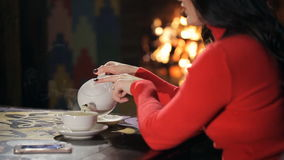 Woman in red gives some tea against background of burning fireplace. stock footage