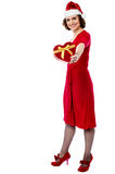 Woman in red giving away xmas gift Royalty Free Stock Image