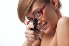 Woman in red glasses taking aim from a gun Royalty Free Stock Image
