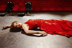 Woman In Red Gown Lying On Stage Stock Image
