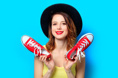 Woman with red gumshoes. Portrait of young smiling red-haired white european woman in hat with gumshoes on blue background Stock Images