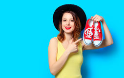 Woman with red gumshoes. Portrait of young smiling red-haired white european woman in hat with gumshoes on blue background Royalty Free Stock Image
