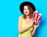 Woman with red gumshoes. Portrait of young smiling red-haired white european woman in hat with gumshoes on blue background Stock Image