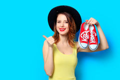 Woman with red gumshoes. Portrait of young smiling red-haired white european woman in hat with gumshoes on blue background Royalty Free Stock Photography