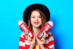 Woman with red gumshoes. Portrait of young smiling red-haired white european woman in hat and red striped shirt with red gumshoes on blue background Stock Image