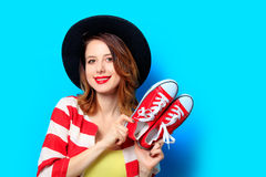 Woman with red gumshoes. Portrait of young smiling red-haired white european woman in hat and red striped shirt with red gumshoes on blue background Stock Photography