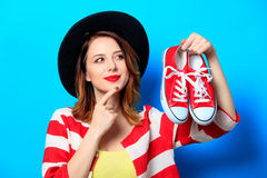 Woman with red gumshoes. Portrait of young smiling red-haired white european woman in hat and red striped shirt with red gumshoes on blue background Stock Photos