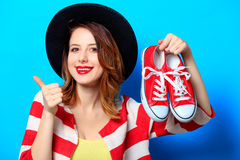 Woman with red gumshoes. Portrait of young smiling red-haired white european woman in hat and red striped shirt with red gumshoes on blue background Stock Images