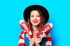 Woman with red gumshoes. Portrait of young smiling red-haired white european woman in hat and red striped shirt with gumshoes ready for shopping on blue Stock Images