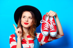 Woman with red gumshoes. Portrait of young smiling red-haired white european woman in hat and red striped shirt with gumshoes ready for shopping on blue Royalty Free Stock Image