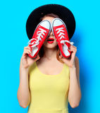 Woman with red gumshoes. Portrait of young surprised red-haired white european woman in hat with gumshoes on blue background Royalty Free Stock Photo